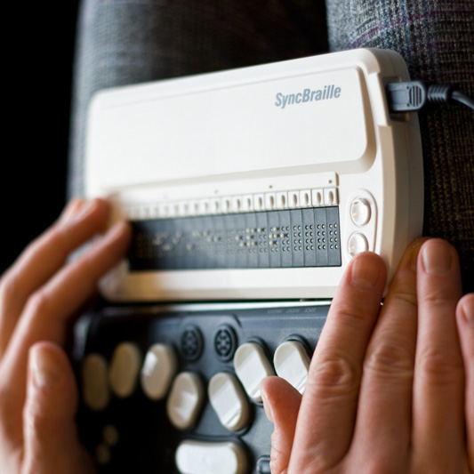 Person using a SyncBraille refreshable braille display